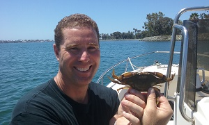 Kevin Hovel on boat holding a swimming crab